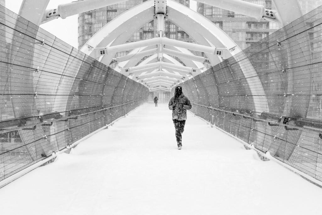 Man Running Across Pedestrian Bridge