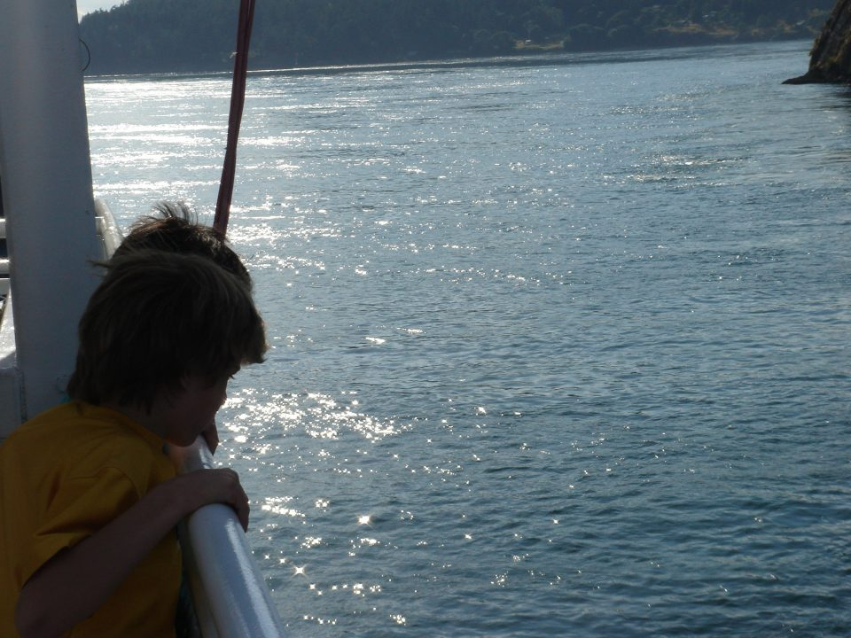 kids look over the edge of the ferry