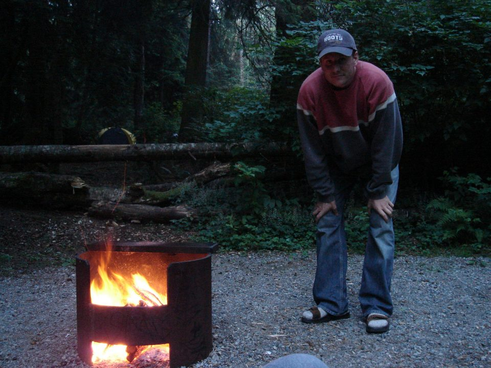 Duncan crouches by his fire