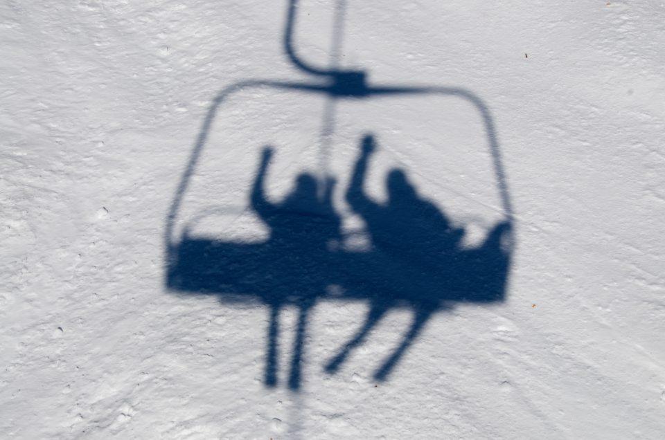 shadow of snow skiers on ski lift