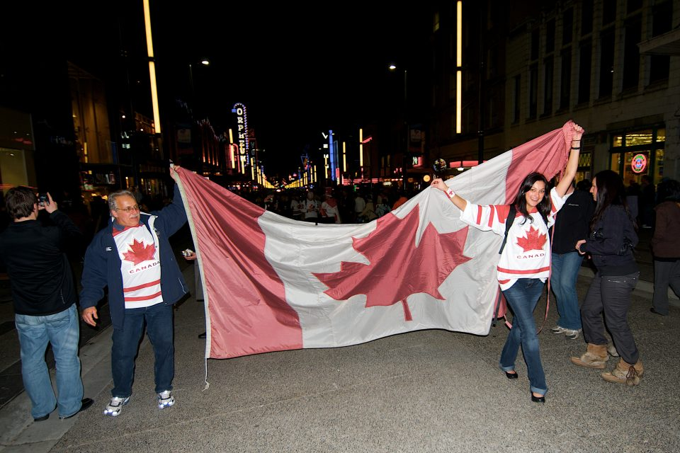Father and Daughter Hold Canadian Flag