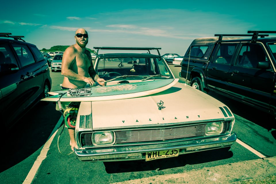 Surfer Waxing His Board On The Hood of a Car Merewether Australia